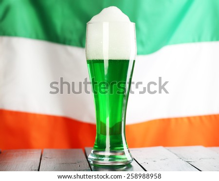 Glass of green beer on flag background - stock photo
