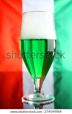 Glass of green beer on Ireland flag background - stock photo