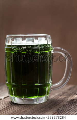 Glass of green beer on vintage wooden background - stock photo