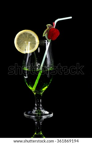 Glass of green drink with bendie and lemon slice on black mirror background - stock photo