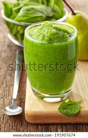 glass of green smoothie on wooden table - stock photo