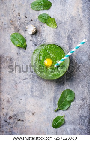 Glass of green smoothie with quail egg's yolk, served with cocktail tube and baby spinach leaves over tin surface. Top view. - stock photo