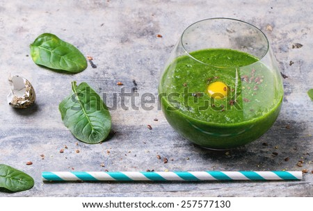 Glass of green smoothie with quail egg's yolk, served with cocktail tube and baby spinach leaves over tin surface. - stock photo