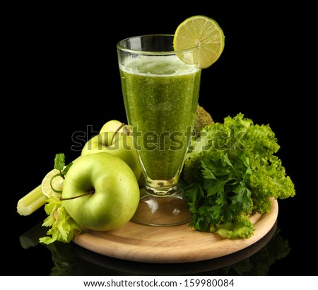 Glass of green vegetable juice and vegetables isolated on black - stock photo