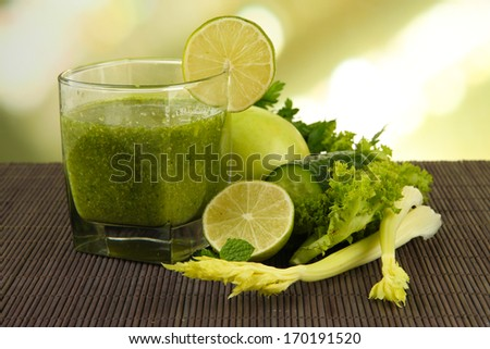 Glass of green vegetable juice and vegetables on bamboo mat on bright background