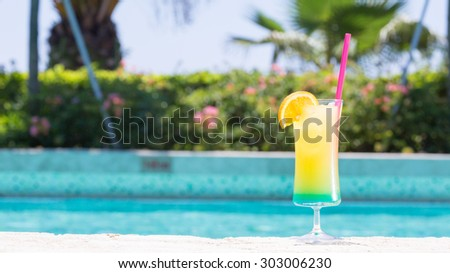 Glass of Happy days non alcohol cocktail on the pool nosing at the tropical resort. Horizontal, cocktail on right side, wide screen - stock photo