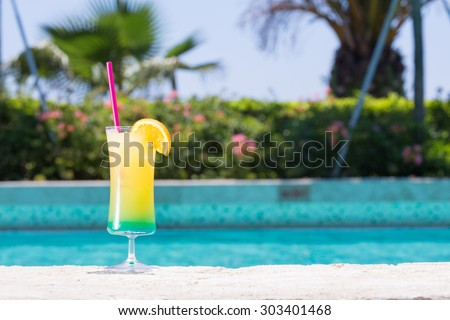 Glass of Happy days non alcohol cocktail on the pool nosing at the tropical resort. Horizontal, cocktail on left side - stock photo