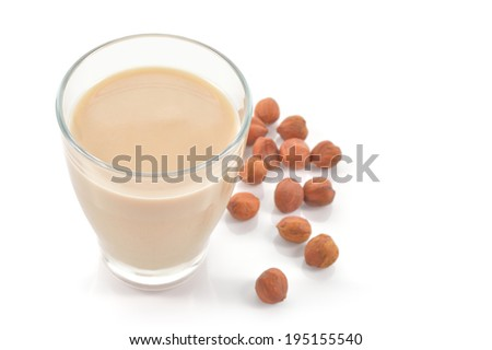 Glass of hazelnut milk or drink as a substitute for dairy milk. Glass of hazelnut milk and hazelnuts isolated on white background.