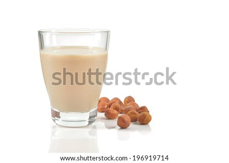 Glass of hazelnut milk or drink as a substitute for dairy milk. Glass of hazelnut milk and hazelnuts isolated on white background. - stock photo
