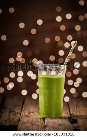 Glass of healthy green vegetable smoothie standing on a rustic restaurant table with a bokeh of party lights in the background - stock photo