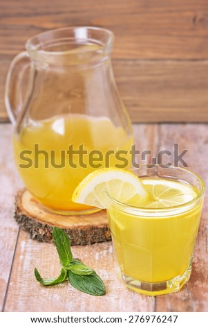 Glass of homemade lemonade and a slice of lemon on a wooden background