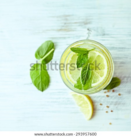 Glass of homemade lemonade with mint and lemon wedges - stock photo