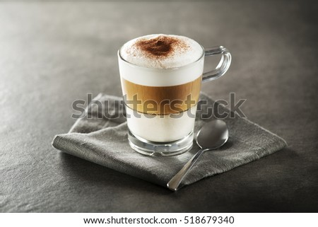 Glass of hot Latte macchiato coffee close up.