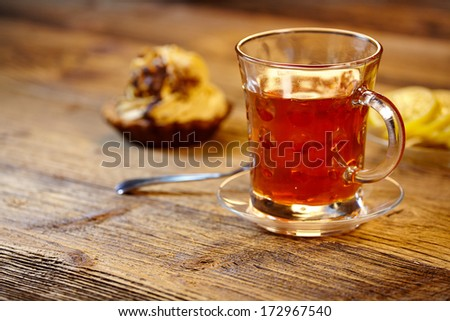 Glass of hot tea on rustic wooden table.