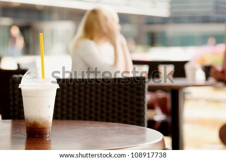 Glass of ice coffee on a table at a cafe with unrecognizable girl out of focus in the background - stock photo