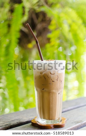 Glass of ice coffee on wooden table