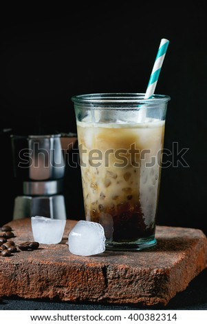 Glass of ice coffee with cream and milk, served with coffee beans, ice cubes and coffee pot on stone board over black textured background. Rustic style. Natural day light - stock photo