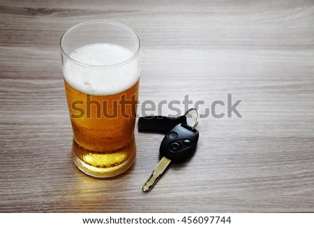 Glass of ice cold beer and car keys./ Drink and Drive./