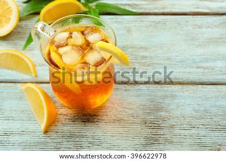 Glass of ice lemon tea on wooden table - stock photo