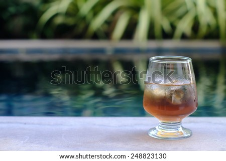 glass of ice tea beside the pool - stock photo