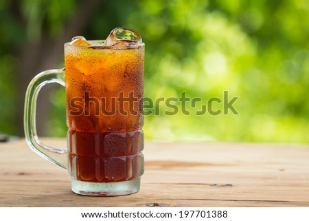 Glass of ice tea on a wooden table - stock photo