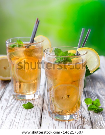 Glass of ice tea with ice-cubes on wooden table
