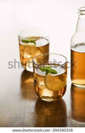 Glass of ice tea with lemon and ice cubes.