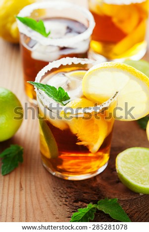 Glass of ice tea with lemon, ice cubes and fresh mint on rustic wooden background, selective focus