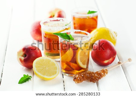 Glass of ice tea with lemon, peach, ice cubes and fresh mint on rustic white wooden background, selective focus