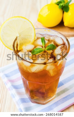 Glass of ice tea with lemons and mint