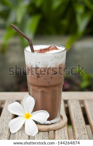 Glass of iced chocolate and white plumeria. - stock photo