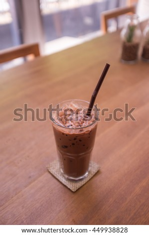 Glass of iced mocha milk coffee on wooden table, selective focus blurred effect for depth of field - stock photo