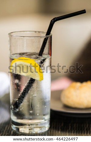 Glass of Iced Still Water With a Straw Ice and Slice of Lemon