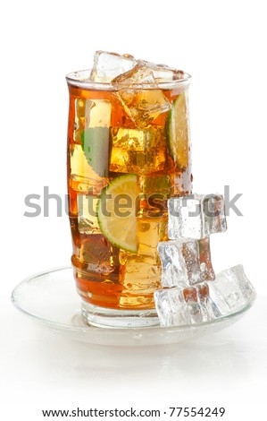 Glass of iced tea with ice cubes, lime and mint, covered with water drops on white wet surface with reflection