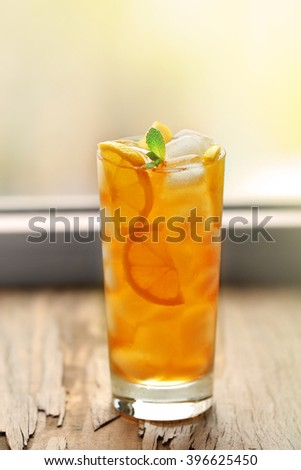 Glass of iced tea with lemon on a windowsill