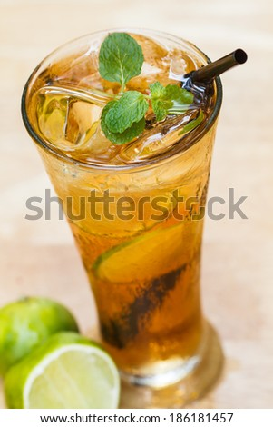 Glass of iced tea with lemon on a wooden table.