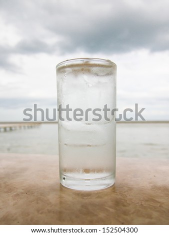 Glass of iced water beside the sea - stock photo