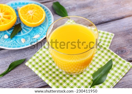 Glass of juice and ripe sweet tangerine on wooden table - stock photo