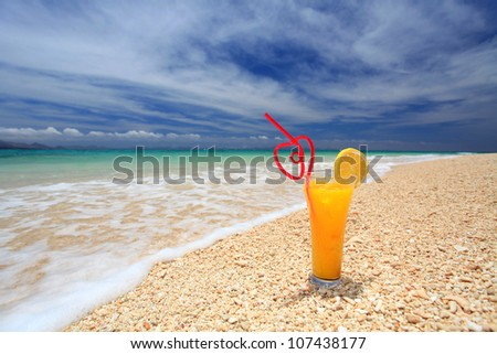 Glass of juice at the beach