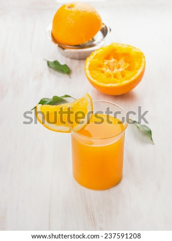 Glass of  juice, squeezed orange and citrus press on white wooden background - stock photo
