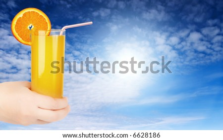 Glass of juice with orange twist and straw in hand against blue sky - stock photo