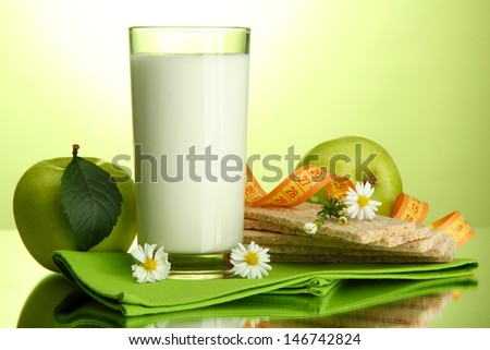 Glass of kefir, apples, crispbreads and measuring tape, on green background
