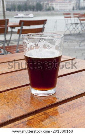 glass of lager beer on wooden table - stock photo