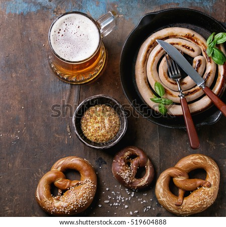 Glass of lager beer with fried sausage in pan with cutlery and traditional salted pretzels and bowl of mustard over old dark wooden background. Top view with space for text. Oktoberfest theme