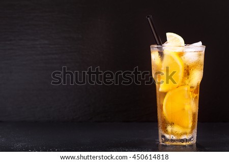 glass of lemon iced tea on dark background - stock photo