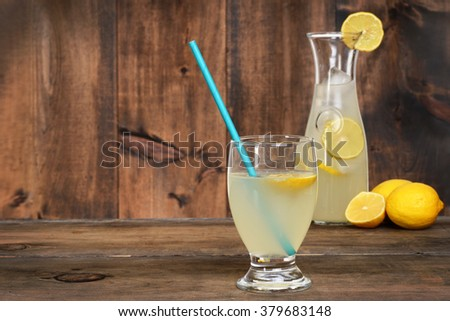 glass of lemonade on wood - stock photo