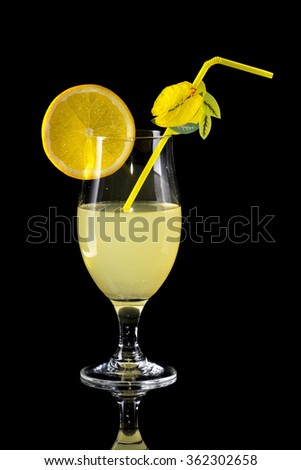 Glass of lemonade with bendie and orange slice on black mirror background with reflection - stock photo