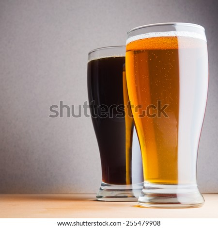 Glass of light and dark beer on blue background