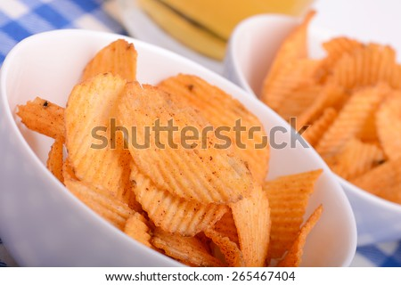 Glass of light beer and potato chips - stock photo
