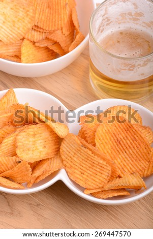 Glass of light beer and potato chips on a wooden table - stock photo